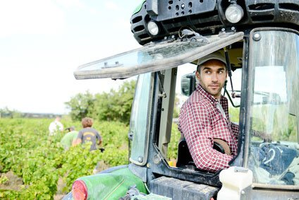 handsome young male farmer driving his tractor during harvest in the field in countryside